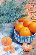 New Year's still life with tangerines, a garland and fir-tree branches. - stock photo