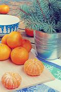 New Year's still life with tangerines and fir-tree branches. - stock photo