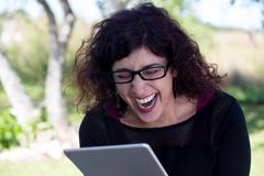 Closeup portrait, happy woman in black shirt and glasses using silver pc, iso Stock Photos
