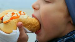 Closeup of child eating hotdog outside in city street. Real time video footage. - stock footage