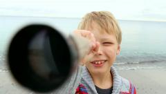 Funny little boy looking through telescope at camera at sea background. Stock Footage