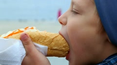Closeup of child eating hotdog outside in city street. Real time video footage. Stock Footage