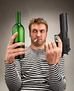 Bizarre sailor choosing between bottle and gun - stock photo