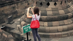 Young woman taking photos of Borobudur temple in Indonesia Stock Footage