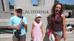 Mother with two children stand near text California in National Mall Stock Footage