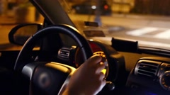 Hands of male driver in small car at night street in town Stock Footage
