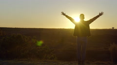 Silhouette Of Man, Looking At Sunset, He Raises His Arms In Celebration - stock footage
