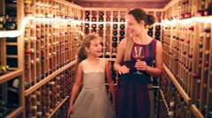 Pretty girl and her mother stand among shelves with wine Stock Footage