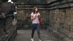 Woman reading guide on smartphone in Borobudur temple in Indonesia Stock Footage