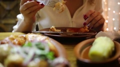 Hands of woman eating grilled meat at table in restaurant - stock footage