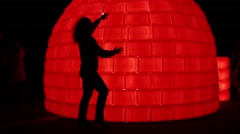 Silhouette of woman posing on red illuminated Eskimo igloo Stock Footage