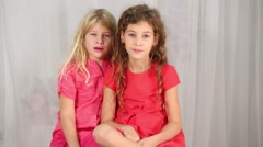 Two pretty girl in red sit together in white studio Stock Footage