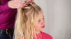 Stock Video Footage of Hands of hairdresser making hairstyle for blonde girl
