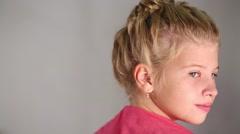 Pretty girl with beautiful hairdo turns head in studio Stock Footage