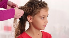 Stock Video Footage of Hands of hairdresser making braid for beautiful girl