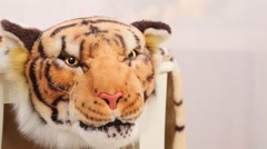 Fierce head of soft costume of yellow tiger on stool in white room Stock Footage