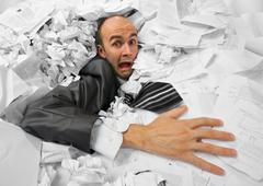 Businessman sinking in heap of documents Stock Photos