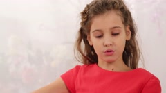 Beautiful girl in red plays soft toy tiger in room Stock Footage