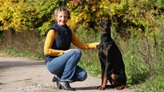 Woman in jeans poses with her dog in sunny autumn forest Stock Footage