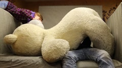 Happy girl and boy play with large toy bear in large armchair Stock Footage