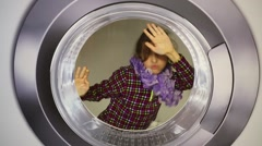 Beautiful girl spinning in huge grey washing machine Stock Footage