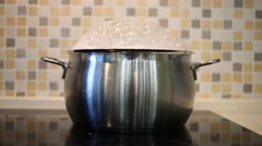 Shiny saucepan of boiling water on stove in kitchen Stock Footage