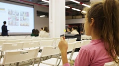 Girl with lollipop sits at conference and listens speaker Stock Footage