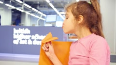 Girl plays with paper plane in British high school of design Stock Footage