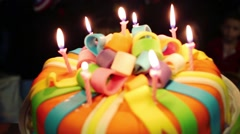 Birthday cake with candles on hands and children out of focus Stock Footage