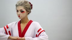 Woman in kimono with make up of geisha poses in studio Stock Footage