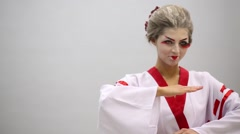 Woman in kimono with make up of geisha takes fighting stance - stock footage