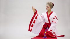 Woman in kimono with make up of geisha sits on floor Stock Footage