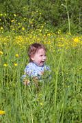 Happy little cute baby sits among on green grass near forest at summer day Stock Photos