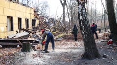 Five workers sawing trees near damaged building in autumn day Stock Footage
