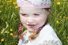 Close up view of little girl is among yellow flowers at meadow at summer day - stock photo