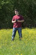 Young man stands with camera among yellow flowers at meadow at summer day Stock Photos