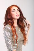 Portrait of beautiful young girl with red hair and shiny silver dress in stud - stock photo