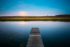 Moonrise over river lake pond in summer evening. Wooden boards p - stock photo
