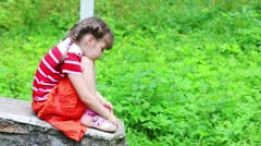 Sad little girl in skirt sits on stone un summer park and turns Stock Footage