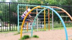 Happy little boy plays on children playground at summer day Stock Footage