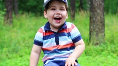 Little cute boy in cap laughs in summer park. Close up view Stock Footage