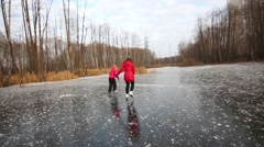Daughter and mother skate on frozen fen among trees Stock Footage