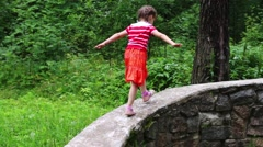 Little cute girl climbs and runs on stone wall in summer park Stock Footage