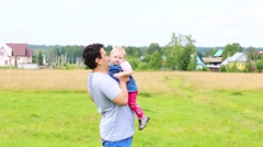 Happy father throws his little daughter at green meadow near village Stock Footage