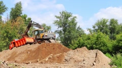 Excavator on hill loading sand into truck in summer Stock Footage