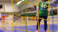 Net and back of goalkeeper out of focus during indoor football game Stock Footage