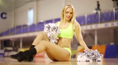 Pretty smiling woman poses with pompoms in empty gym hall - stock footage