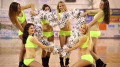 Six smiling women show heart shape of pompoms in gym hall - stock footage