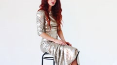 Beautiful young woman in shiny dress sits on stool Stock Footage