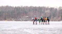 Seven young people skate on natural ice rink as train Stock Footage
